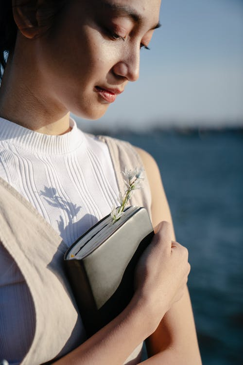 Woman in White and Blue Shirt Holding Book
