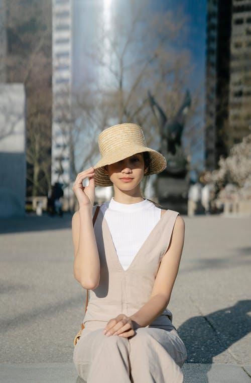 Woman in White Tank Top and Brown Straw Hat Standing on Road
