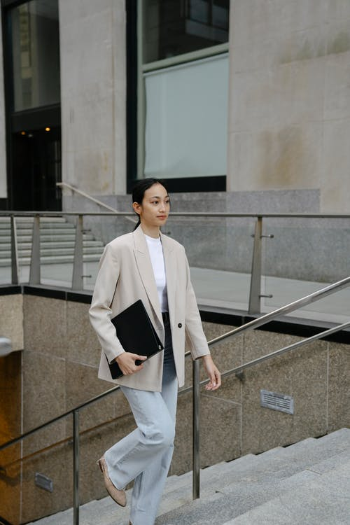 Woman in White Blazer and White Pants Standing on Gray Concrete Stairs