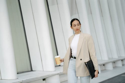 Woman in Beige Blazer and White Dress Pants Standing Near White Wall