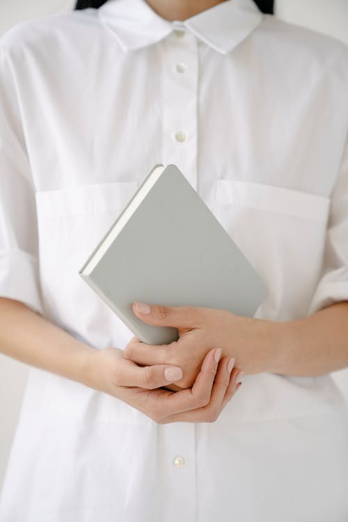 Person Holding White Paper on White Textile