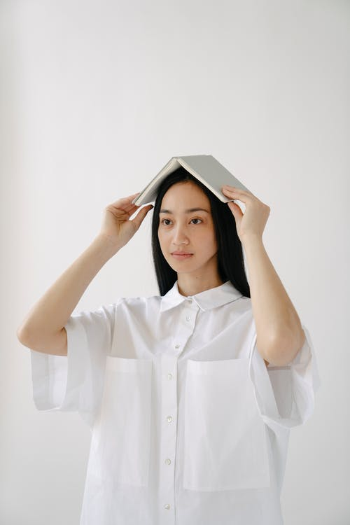 Woman in White Button Up Shirt Covering Her Face With Her Hands