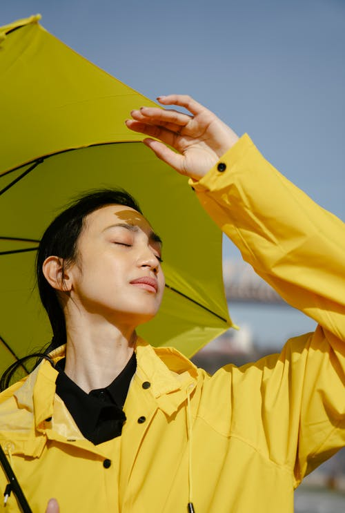 Woman in Yellow Coat Holding Umbrella