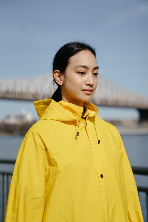 Woman in Yellow Hoodie Standing Near Body of Water