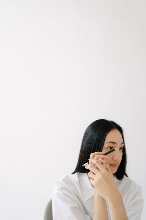 Woman in White Long Sleeve Shirt Covering Her Face With Her Hand