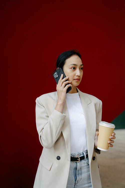 Woman in White Blazer Holding Phone