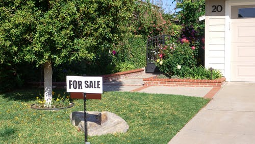For Sale Sign on Green Grass Lawn