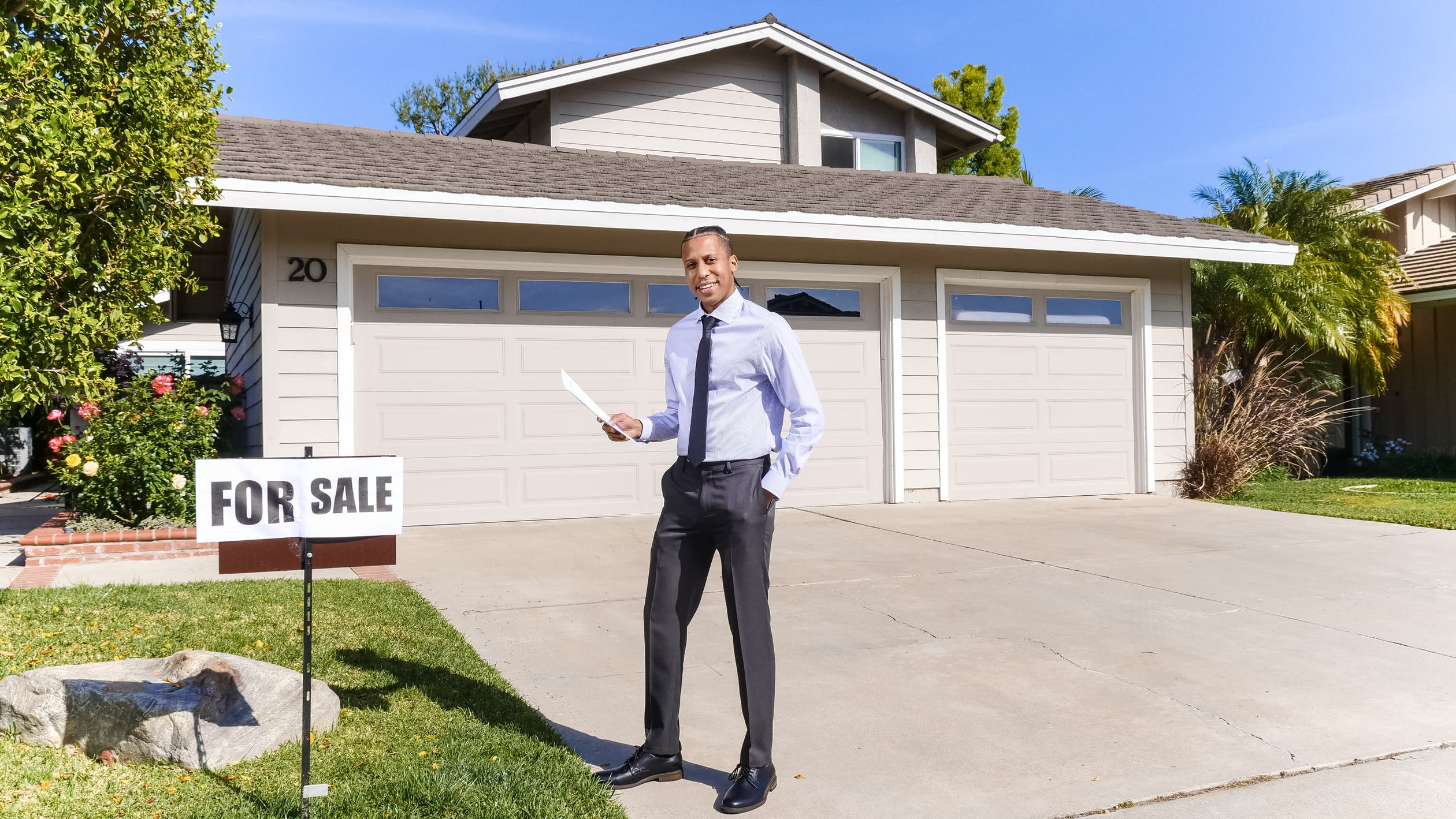 A man standing in front of the house for sale