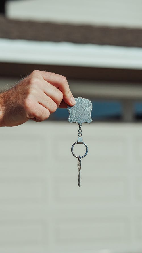 Person Holding Gray Metal Key