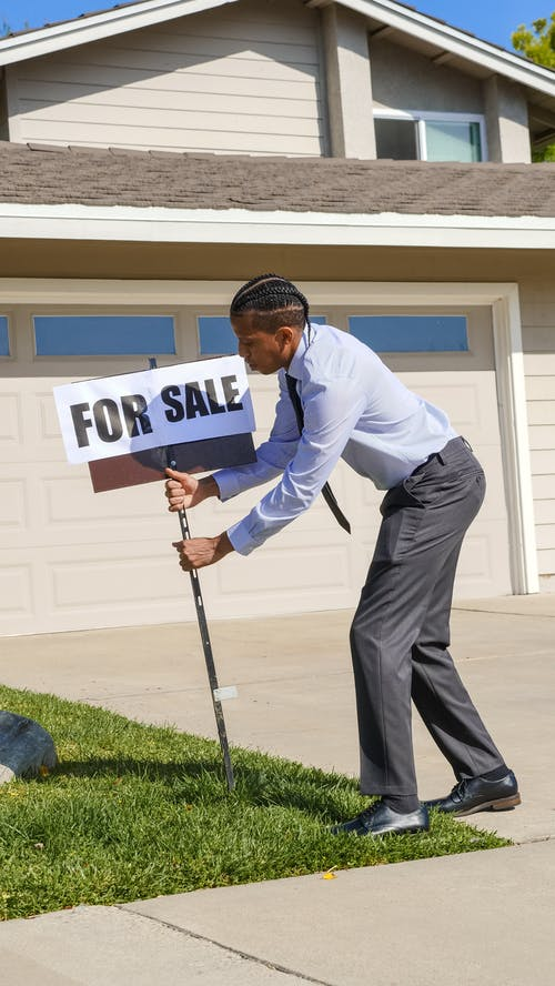 Man Holding a For Sale Signage