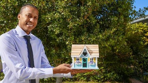 Man in Dress Shirt Holding a Miniature Wooden House