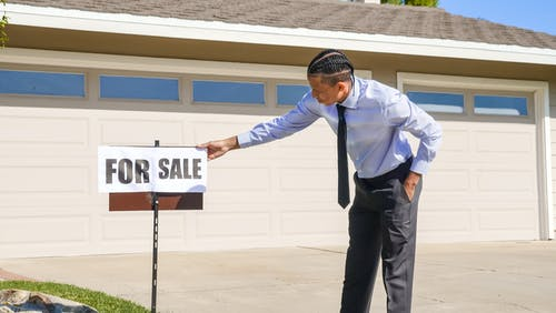Man in a Dress Shirt Holding a For Sale Signage