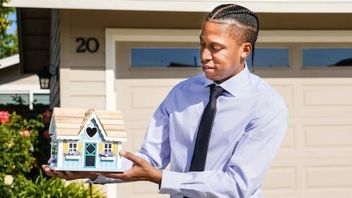 Man in a Dress Shirt Holding a Miniature House