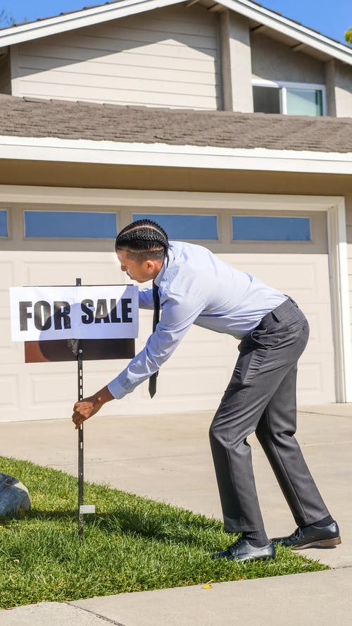 Man Fixing a For Sale Sign