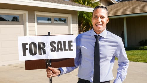 Man in Blue Dress Shirt Holding a For Sale Sign