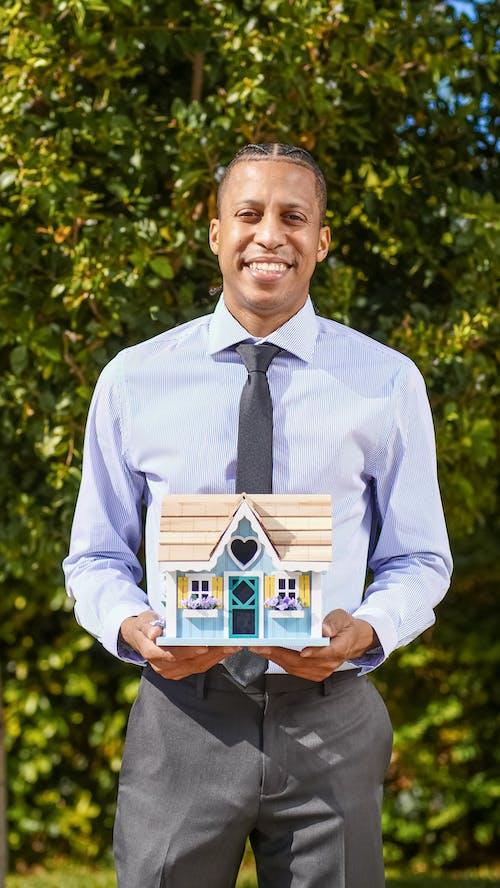 Man in Blue Dress Shirt Holding a Miniature Wooden House