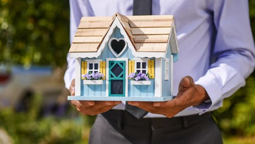 Person Holding a Miniature Wooden House