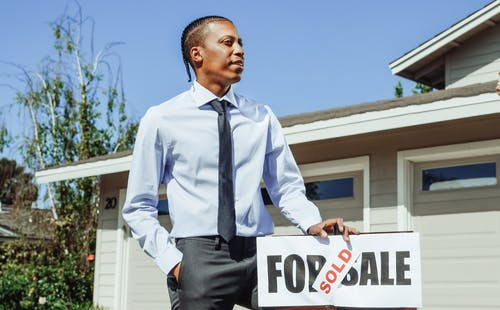 Man in Dress Shirt and Black Necktie Holding on a Sold Sign
