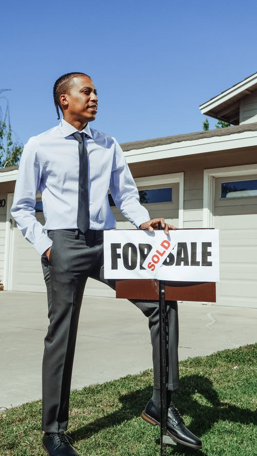 Man in Blue Dress Shirt Holding a Sold Sign