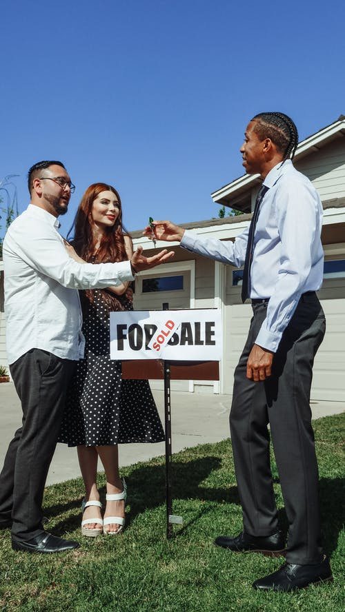 Man in Dress Shirt Handing House Key to a Couple