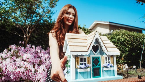 Woman Holding a Miniature Wooden House