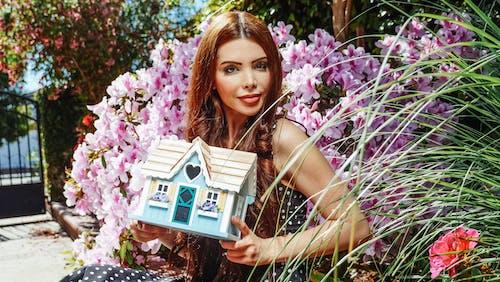Woman Holding a Miniature House