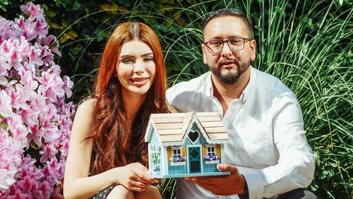 Couple Holding Miniature House