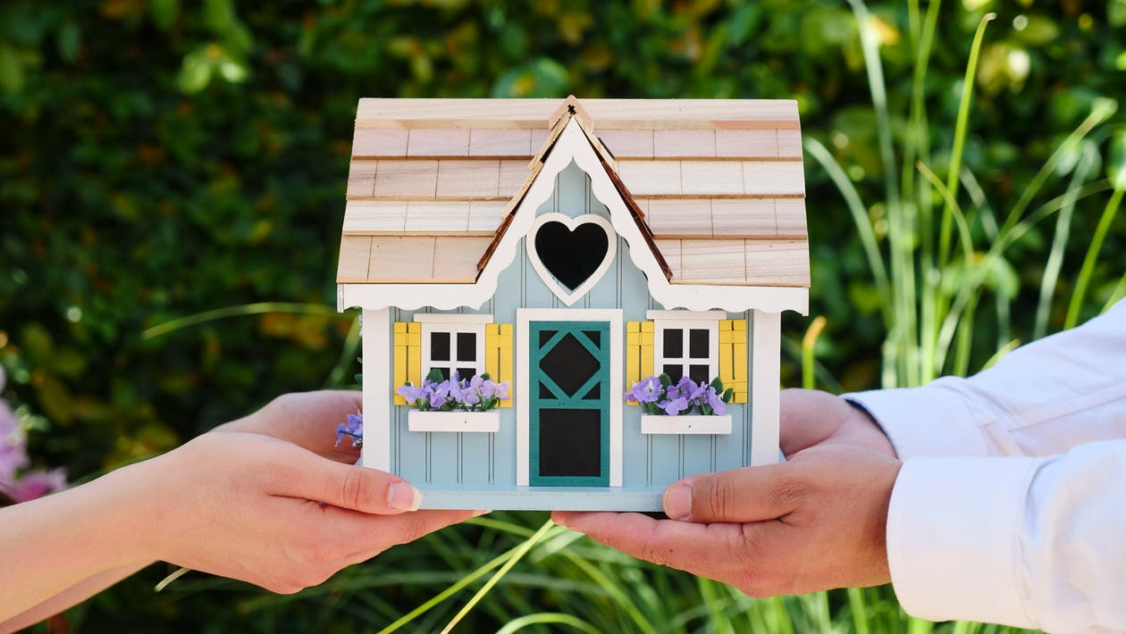 People Holding Miniature Wooden House