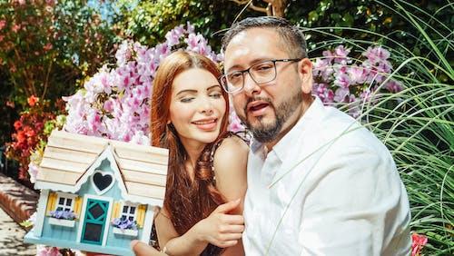 Man Sitting Beside a Woman Holding a Miniature House