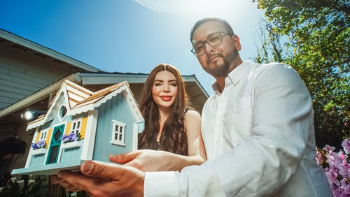 Man and Woman Holding a Miniature House