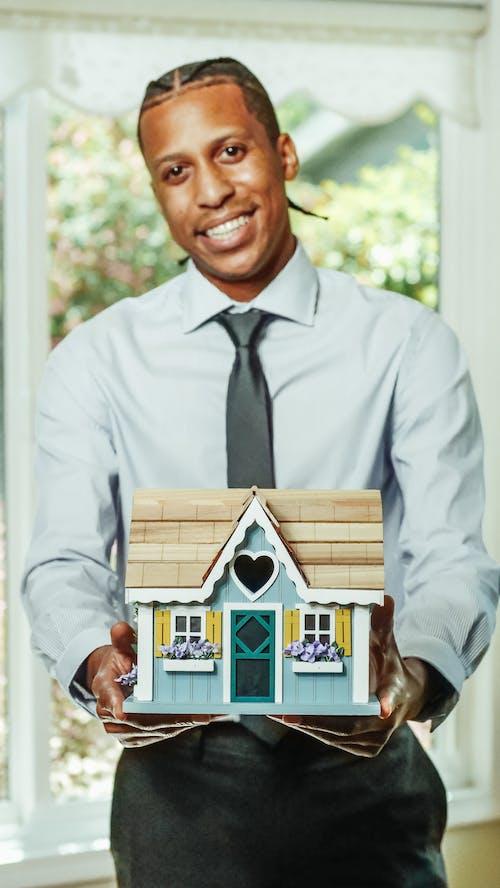 Man in Dress Shirt Holding Miniature Wooden House