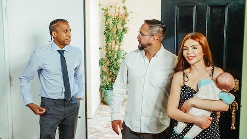 Man in Blue Dress Shirt Standing Beside a Couple