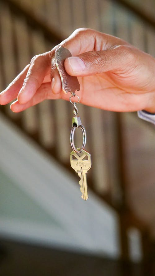 Person Holding Gold Key Chain
