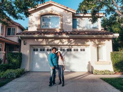 Couple Standing In Front of their House