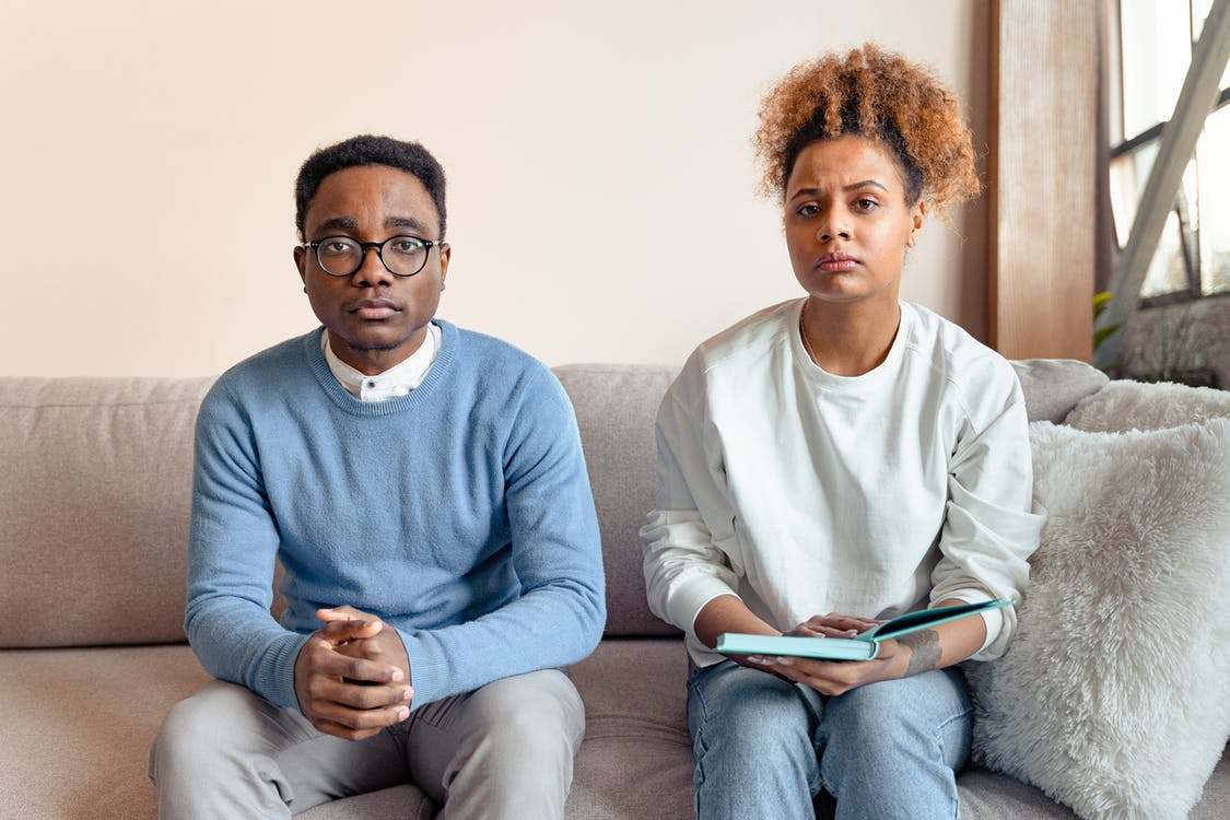 A Couple Frowning while Sitting at a Couch