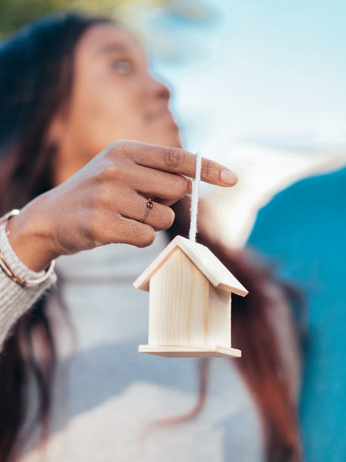 Woman Holding Miniature Wooden House