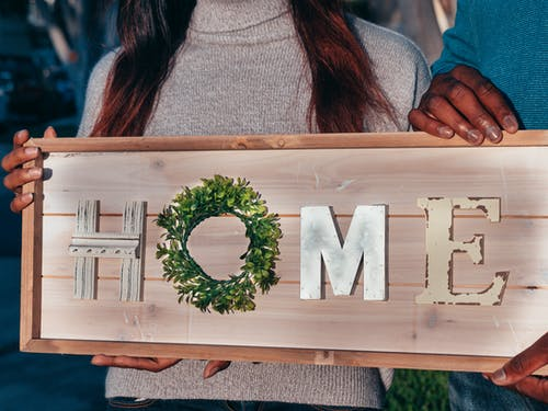 People Holding a Wooden Home Decoration
