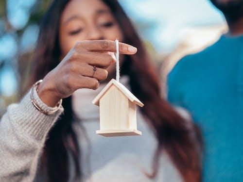 Woman Holding a Wooden Bird House