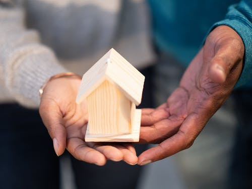 Person Holding Miniature Wooden House