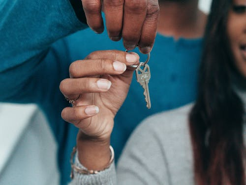 Person Holding Gold Cross Pendant