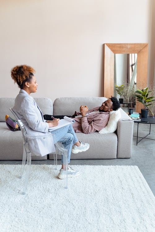 2 Women Sitting on Gray Couch