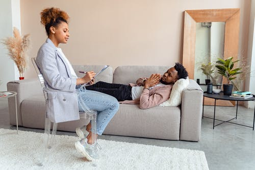 Man and Woman Sitting on Gray Couch