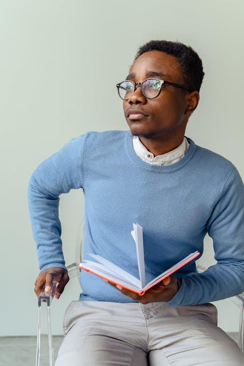 Man in Blue Sweater Wearing Black Framed Eyeglasses Holding White Paper