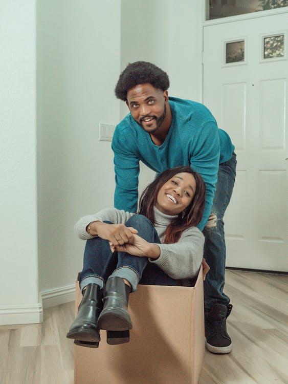 Man in Blue Long Sleeve Shirt Pushing Woman Inside a Box