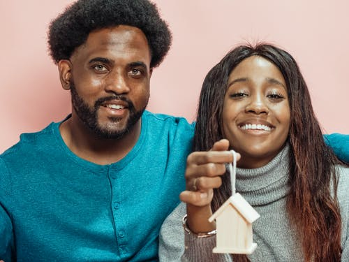 Couple Smiling while Holding a Miniature Wooden House