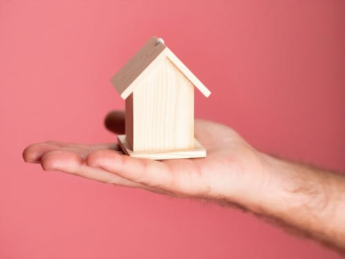 Person Holding Brown Miniature Wooden House