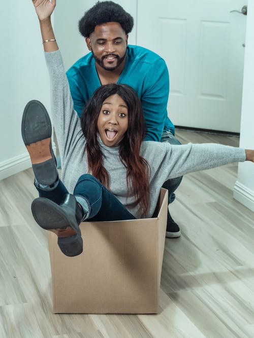 Man Pushing Woman Inside a Box