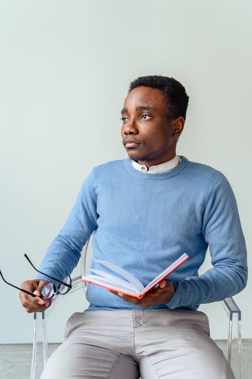 Man in Blue Long Sleeve Shirt Holding Pen