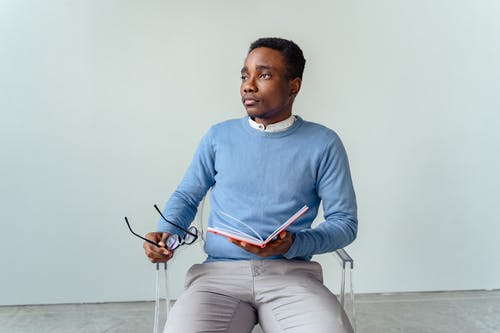Man in Blue Sweater and Gray Pants Sitting on White Chair