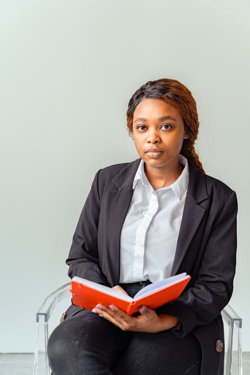 Woman in Black Blazer Holding a Book
